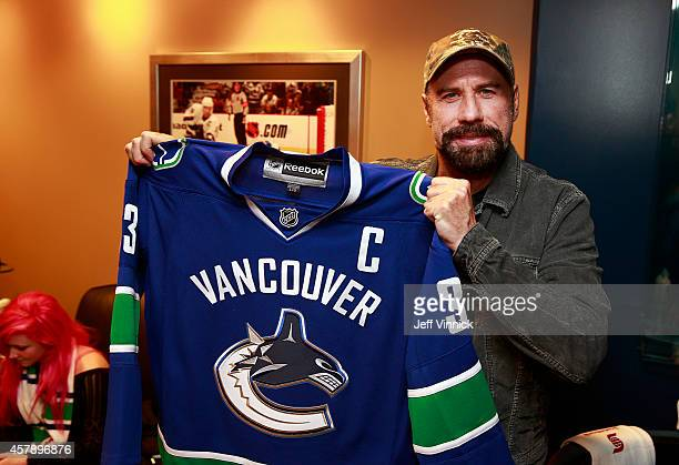 Actor John Travolta holds a Vancouver Canucks jersey during the NHL game between the Vancouver Canucks and the Tampa Bay Lightning at Rogers Arena...