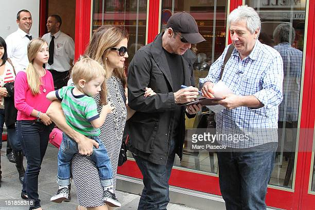 Actor John Travolta signs autographs as he and his wife Kelly Preston their son Benjamin and their daughter Ella Bleue are seen leaving the 'Pizza...