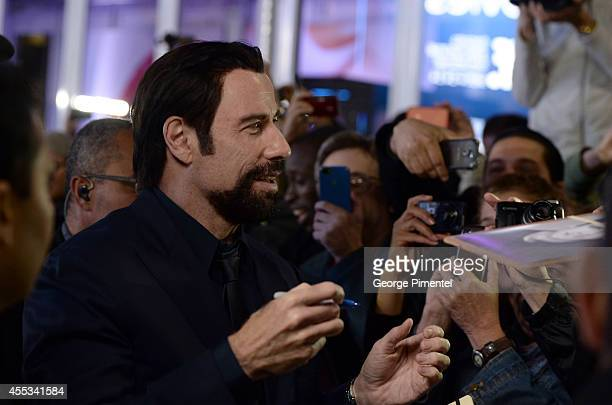 Actor John Travolta signs autographs as he attends 'The Forger' premiere during the 2014 Toronto International Film Festival at Roy Thomson Hall on...