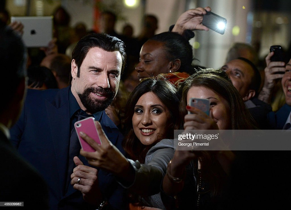 Actor John Travolta takes a selfie with fans as he attends 'The Forger' premiere during the 2014 Toronto International Film Festival at Roy Thomson Hall on September 12, 2014 in Toronto, Canada.