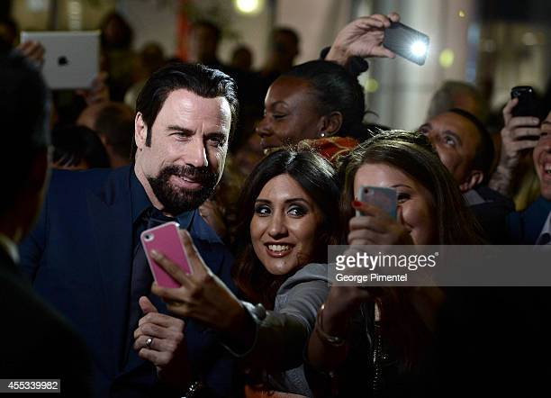 Actor John Travolta takes a selfie with fans as he attends 'The Forger' premiere during the 2014 Toronto International Film Festival at Roy Thomson...
