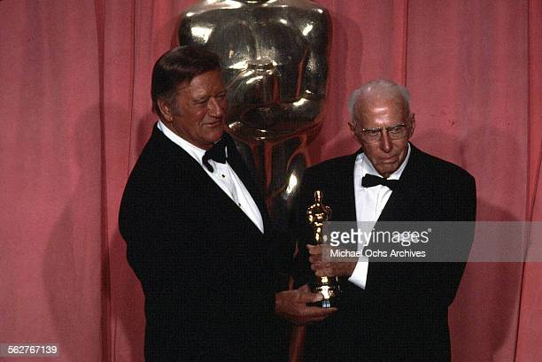 Actor John Wayne and Director Howard Hawks Academy Honorary Award winner pose backstage during the 47th Academy Awards at Dorothy Chandler Pavilion...