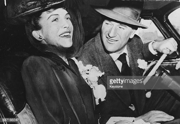 Actor John Wayne and his wife Esperanza Baur smiling in their car following their wedding 1945