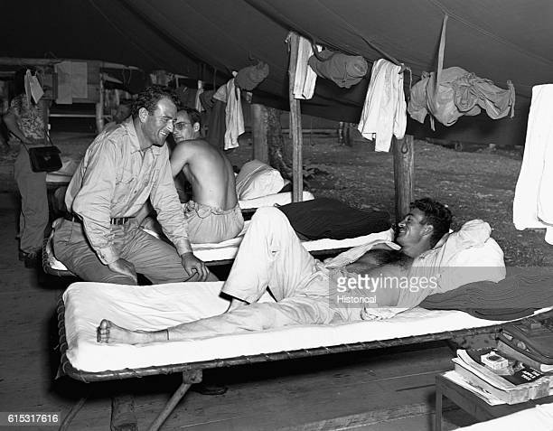 Actor John Wayne chats with a soldier lying on his bunk New Guinea 1944