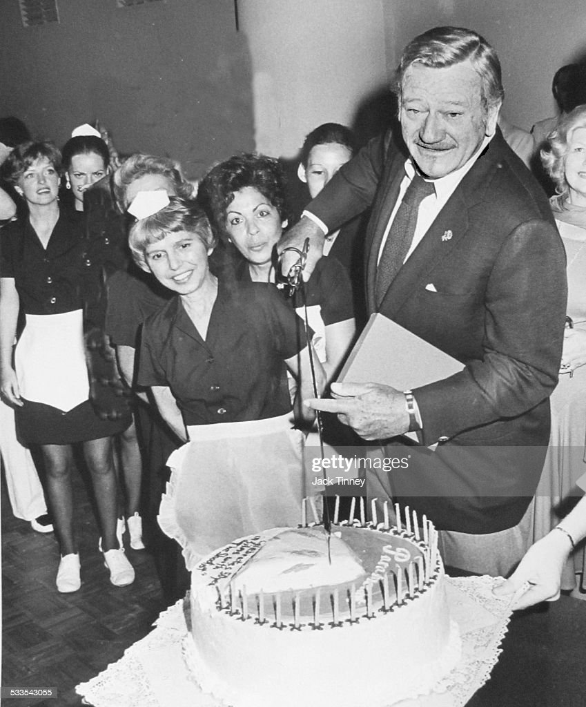 Actor John Wayne Cutting A Cake During A Celebration Of His Fifty