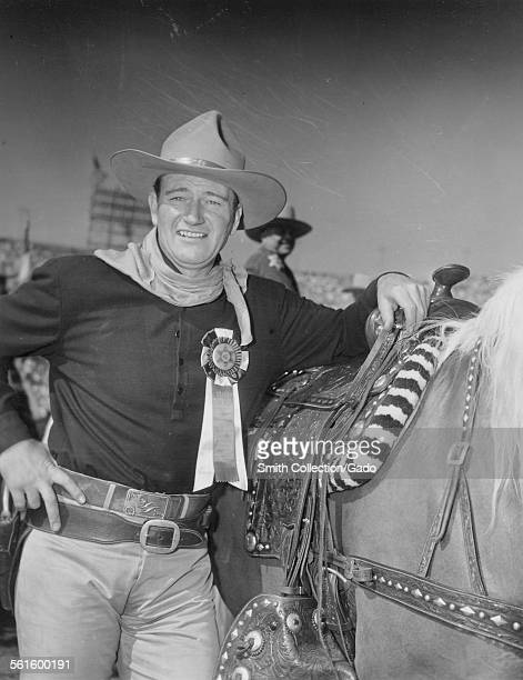Actor John Wayne wearing a cowboy hat with hands on hips standing with a horse and a medal 1954