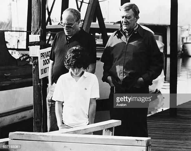 Actor John Wayne with his son Ethan and director John Sturges saying their prayers together on the set of the movie 'McQ' in Seattle Washington...