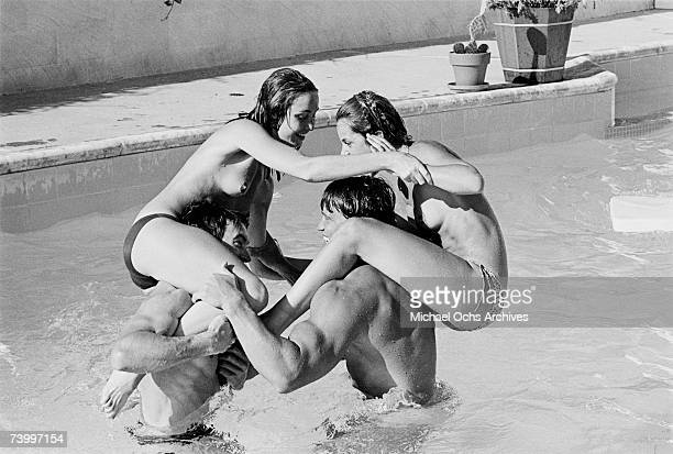 Actor and body builder Arnold Schwarzenegger plays with a topless Nastassja Kinski on his shoulders in a pool in 1976 in Los Angeles California