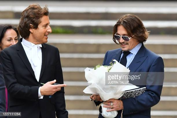 Actor Johnny Depp carries a bunch of flowers given to him by a fan, as he takes leave of a member of his legal team outside court after the sixth day...