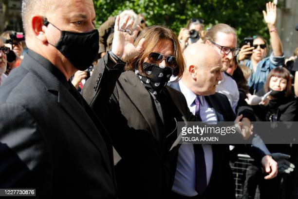 Actor Johnny Depp geatures as he arrives to attend day twelve of his libel trial against News Group Newspapers , at the High Court in London, on July...