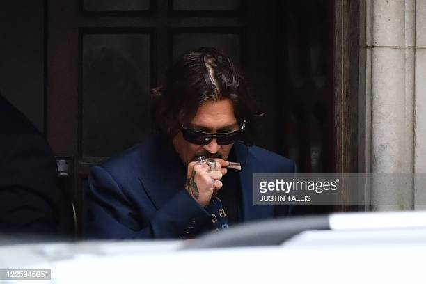 TOPSHOT US actor Johnny Depp gestures as he leaves on the third day of his libel trial against News Group Newspapers at the High Court in London on...