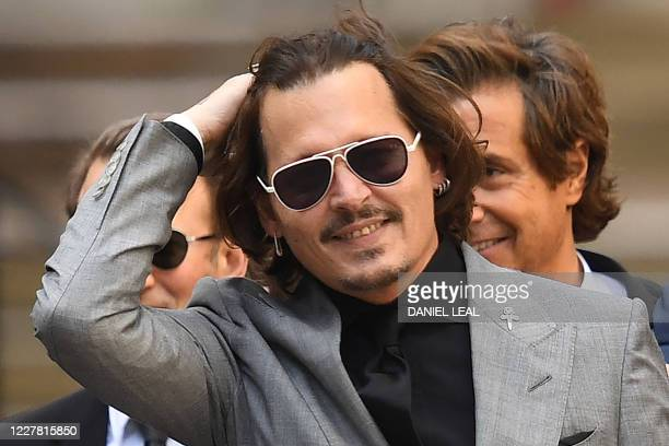 Actor Johnny Depp gestures as he leaves the High Court after the final day of his libel trial against News Group Newspapers , in London, on July 28,...