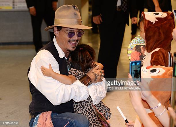 US actor Johnny Depp hugs twoyearold Rina Funase as her sister Mana looks on upon his arrival at the Narita International airport in Narita Chiba...