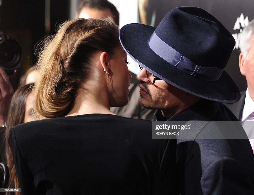 Actor Johnny Depp (R) leans over to kiss actress Amber Heard (L) as they attend the US premiere of '3 Days To Kill,' at Arclight Cinemas, February 12, 2014 in Hollywood, California.