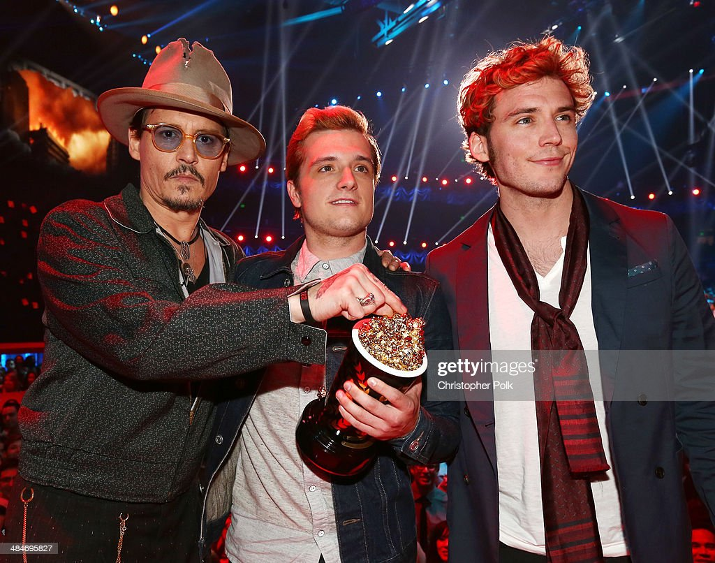 Actor Johnny Depp poses with actors Josh Hutcherson and Sam Claflin, winners of the Movie of the Year award for 'The Hunger Games: Catching Fire,' at the 2014 MTV Movie Awards at Nokia Theatre L.A. Live on April 13, 2014 in Los Angeles, California.
