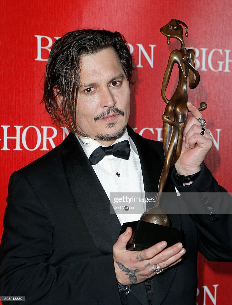 Actor Johnny Depp poses with the Desert Palm Achievement Award during the 27th Annual Palm Springs International Film Festival Awards Gala at Palm Springs Convention Center on January 2, 2016 in Palm Springs, California.