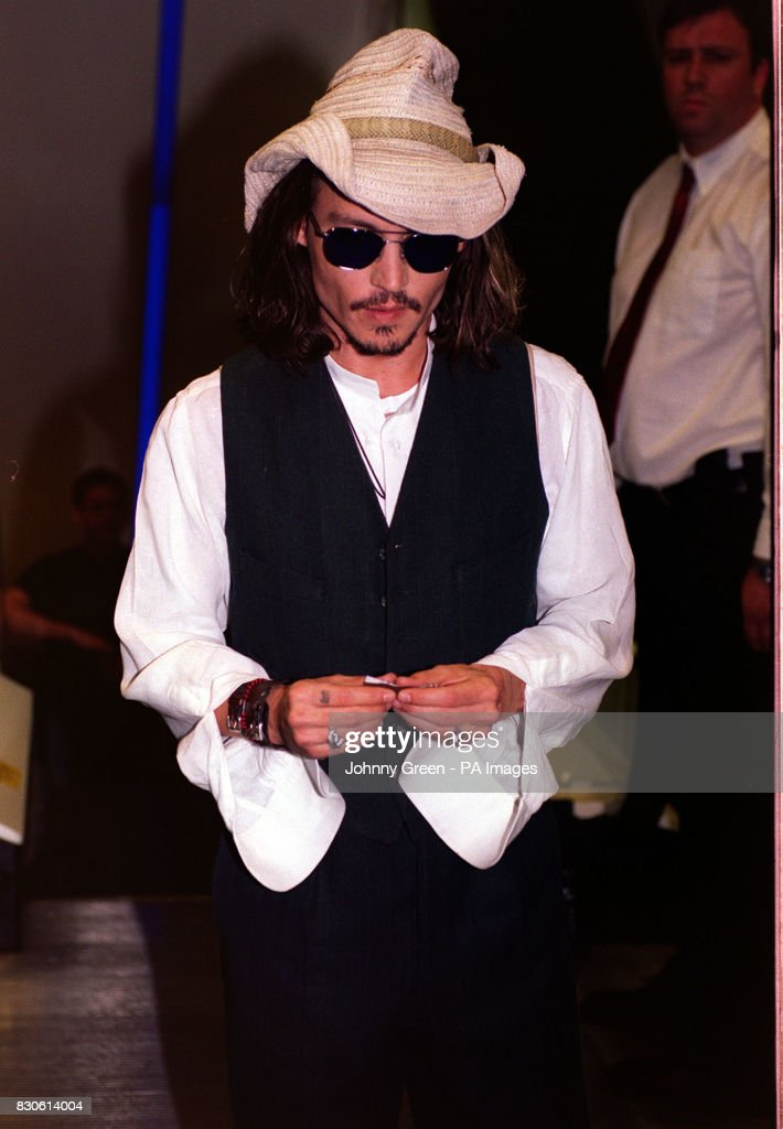 Actor Johnny Depp 37 Rolls A Cigarette As He Arrives For The Premiere Of