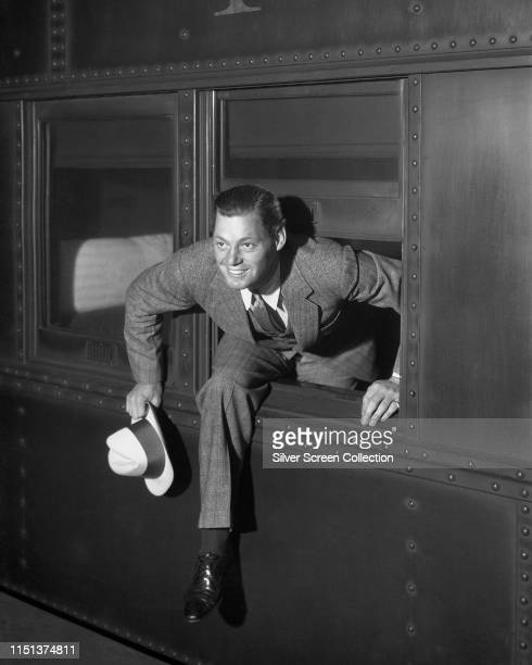 Actor Johnny Weissmuller climbing out of a train window circa 1940