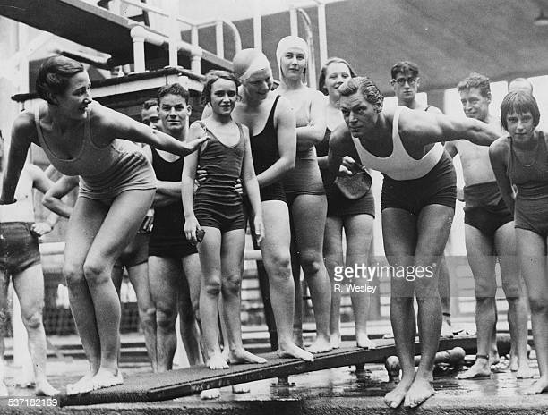 Actor Johnny Weissmuller in a dive position at the start of a swimming race with a group of bathers at the Empire Pool Wembley London October 7th 1934