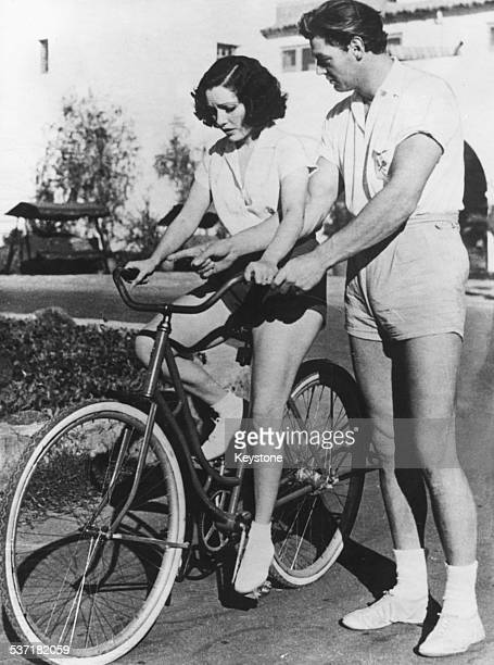 Actor Johnny Weissmuller teaching actress Lupe Velez how to ride a bicycle December 22nd 1932