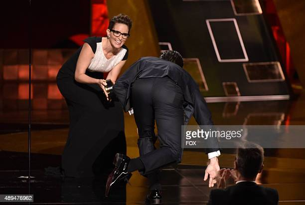 Actor Jon Hamm accepts Outstanding Lead Actor in a Drama Series award for 'Mad Men' from actress Tina Fey onstage during the 67th Annual Primetime...