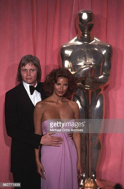 Actor Jon Voight and actress Raquel Welch poses backstage after presenting ' Best Cinematography' award during the 47th Academy Awards at Dorothy...