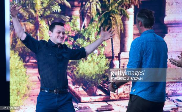Actor Joseph GordonLevitt gestures while greeting Guillame Brunier senior producer from Ubisoft Montpellier at the Ubisoft E3 2018 media briefing...