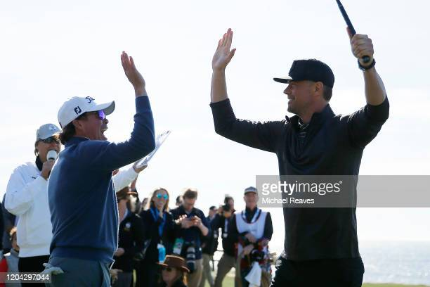 Actor Josh Duhamel celebrates with music artist Clay Walker after playing his shot from the 18th tee during the 3M Celebrity Challenge prior to the...