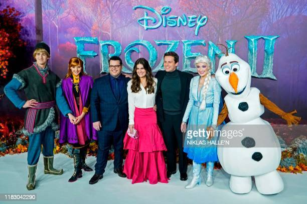 US actor Josh Gad US actor Idina Menzel and US actor Jonathan Groff pose with people dressed as characters from the film on the red carpet as they...