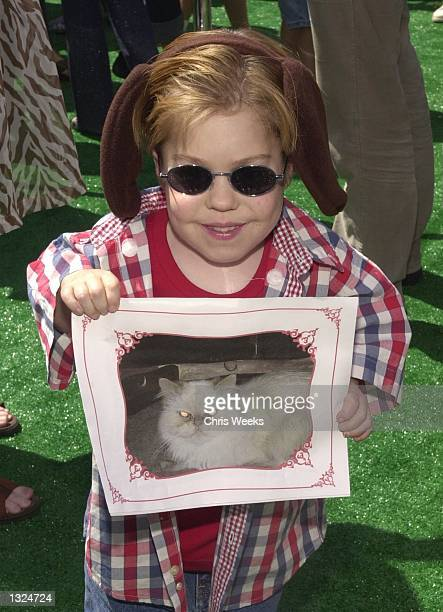 Actor Josh Ryan Evans holds a photo of a cat as he arrives at the world premiere of Warner Bros Pictures'' Cats and Dogs June 23 2001 at the Mann''s...