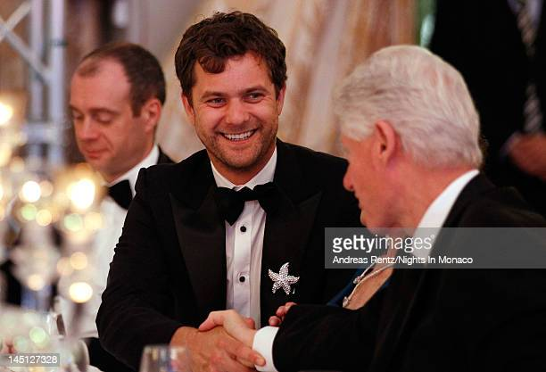 Actor Joshua Jackson celebrates with former US President Bill Clinton after bidding and winning a Carla Amorim necklace in the auction for girlfriend...