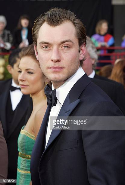 Actor Jude Law nominated for Best Actor in a Leading Role for his performance in Cold Mountain and his girlfriend Sienna Miller attend the 76th...