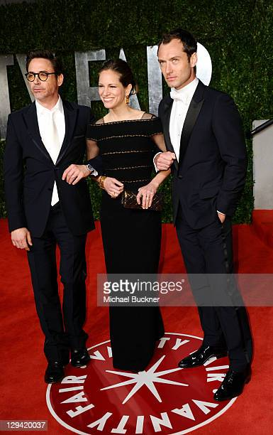 Actor Jude Law producer Susan Downey and actor Robert Downey Jr arrives at the Vanity Fair Oscar party hosted by Graydon Carter held at Sunset Tower...