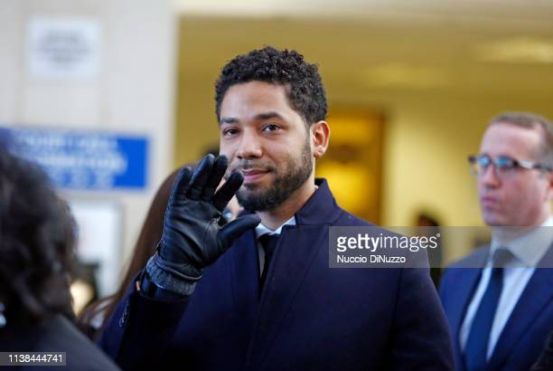 Actor Jussie Smollett waves as he follows his attorney to the microphones after his court appearance at Leighton Courthouse on March 26 2019 in...