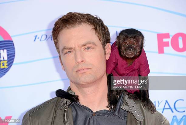 Actor Justin Kirk and Crystal the Monkey arrive at the 2012 Teen Choice Awards at Gibson Amphitheatre on July 22 2012 in Universal City California