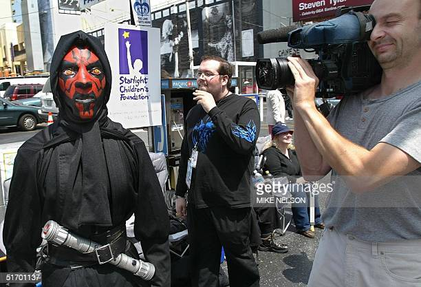 Actor Kato Salem dressed as Star Wars' character Darth Maul is filmed by Germany Focus TV as Star Wars fans wait outside the Mann's Chinese Theater...