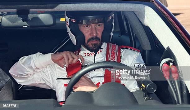 Actor Keanu Reeves buckles his seat belt during the press practice day for the Toyota Pro/Celebrity Race on April 6 2010 in Long Beach California
