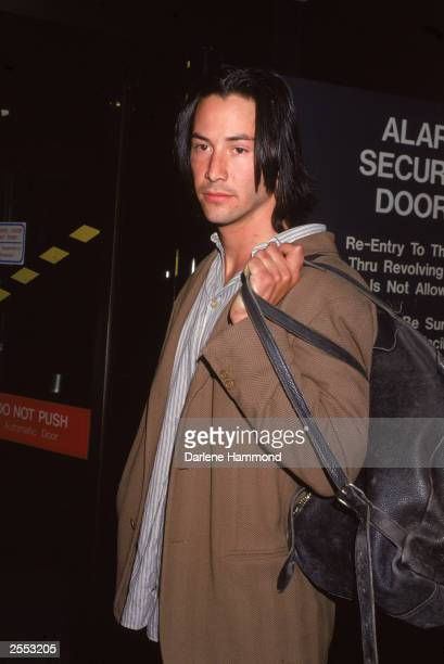 Actor Keanu Reeves holds a bag over his shoulder c 1993