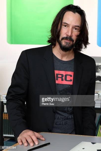 Actor Keanu Reeves is seen posing by his book Ode to happiness during Paris Photo at le Grand Palais on November 10 2017 in Paris France