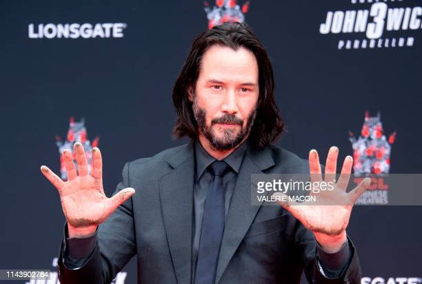 Actor Keanu Reeves shows his hands after placing them in cement during his handprint ceremony at the TCL Chinese Theatre IMAX forecourt on May 14...