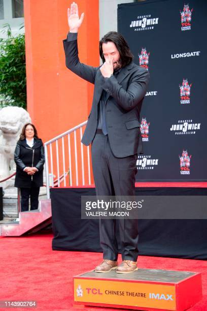 Actor Keanu Reeves stands in cement during his handprint ceremony at the TCL Chinese Theatre IMAX forecourt on May 14 2019 in Hollywood California