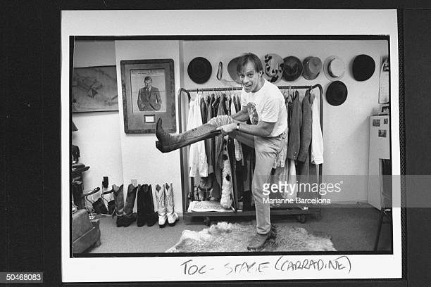 Actor Keith Carradine pulling on his boots in dressing room at the Palace Theater where he is starring in musical The Will Rogers Follies
