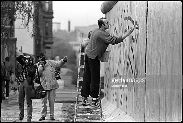 Actor Keith Haring painting the wall nearby Checkpoint Charlie WestBerlin 1986