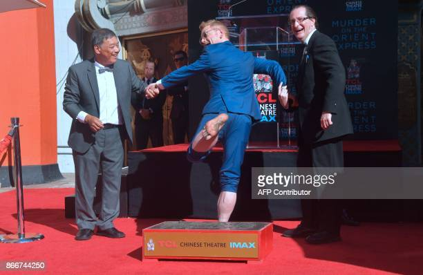 Actor Kenneth Branagh displays his foot after placing his feet into the block of cement at his Hand and Footprints Ceremony in front of the TCL...
