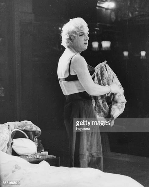 Actor Kenneth More dressed as a woman on stage undressing in a bedroom farce during rehearsals for the 'Night of 100 Stars Charity Show' in which he...