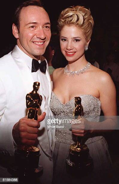 Actor Kevin Spacey and actress Mira Sorvino hold the Oscars they won for best supporting actor and actress They're attending the Governor's Ball...