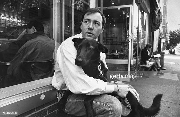 Actor Kevin Spacey holding his black dog while sitting on bench outside restaurant