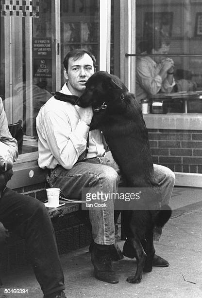 Actor Kevin Spacey petting his black dog while sitting on bench outside restaurant
