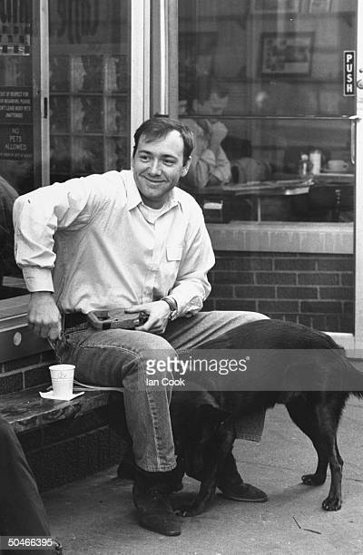 Actor Kevin Spacey sitting on bench w his black dog outside restaurant