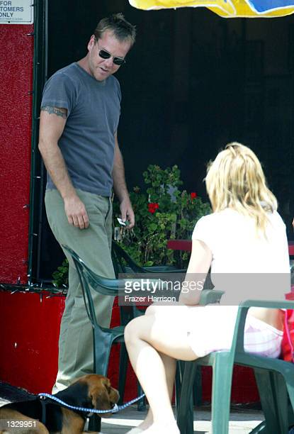 Actor Kiefer Sutherland admires a customers dog while leaving Albano's Brooklyn Pizzeria on August 3 2002 in Los Angeles California